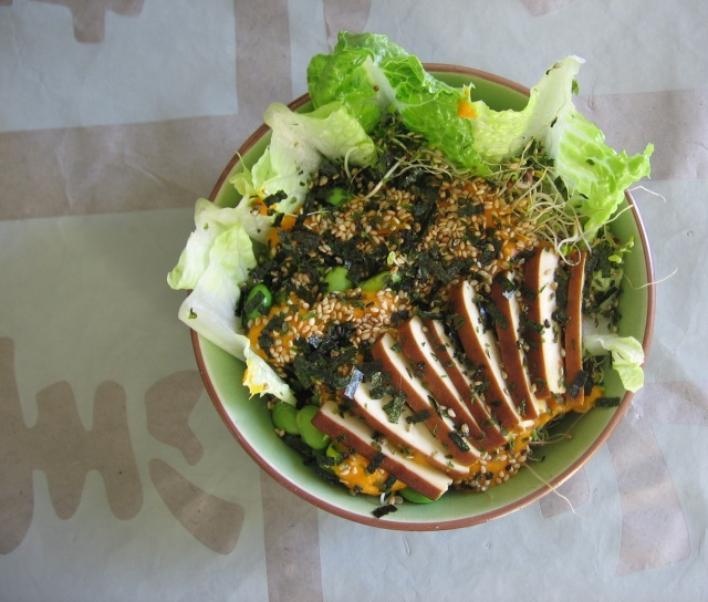 A bowl filled with quinoa, lettuce, sprouts, edamame, and smoked tofu with an orange-colored dressing, sprinkled with nori and sesame seeds.