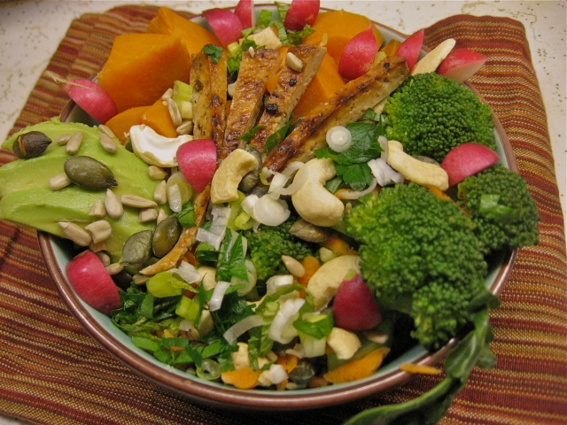 A bowl stuffed with artfully arranged sweet potato, avocado, broccoli, radishes, and broiled tofu, sprinkled with cashews, pumpkin seeds and sunflower seeds.