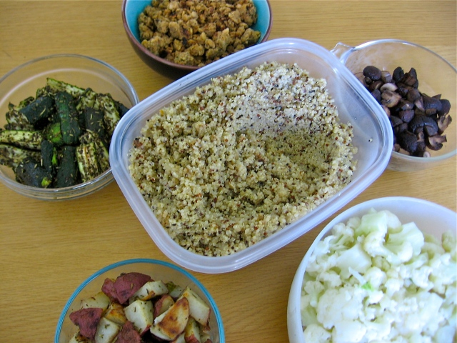 A bowl of quinoa surrounded by dishes of steamed cauliflower, roasted mushrooms, roasted new potatoes, roasted zucchini with herbs, and tempeh-bean sausage crumbles